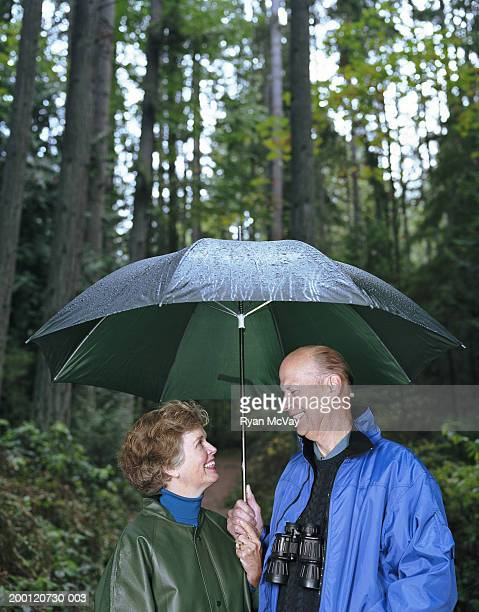 Mature man and woman standing under umbrella in forest, smiling
