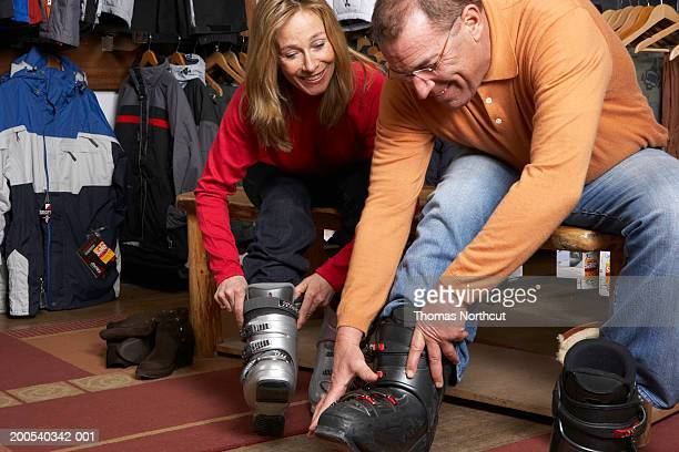 Mature man and woman trying on ski boots in sports shop