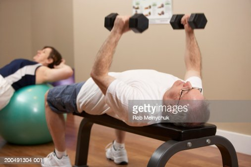 Mature man and woman working out in gym (focus on man lifting weights) : Stock Photo