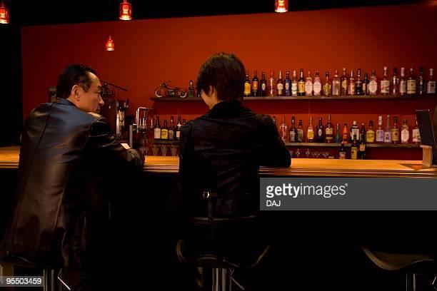 Mature man and young woman at bar counter
