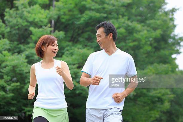 Mature man and young woman running