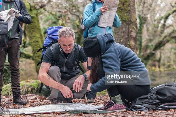 Mature man and young woman studying map