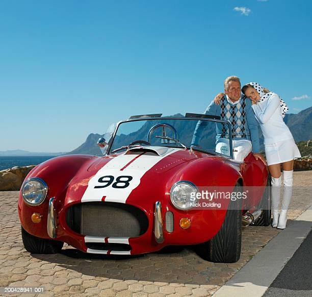 Mature man and young woman with classic racing car on coast road