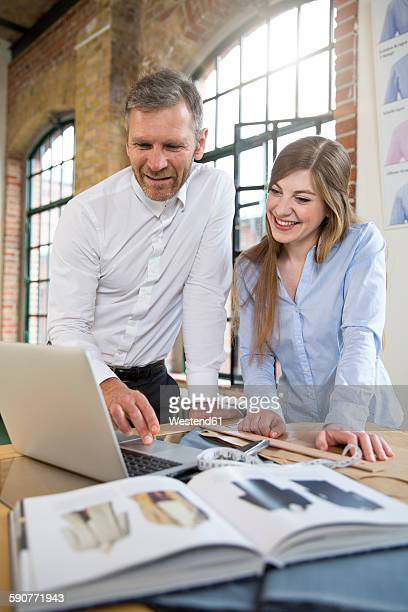 Mature man and young woman working together at tailoring shop