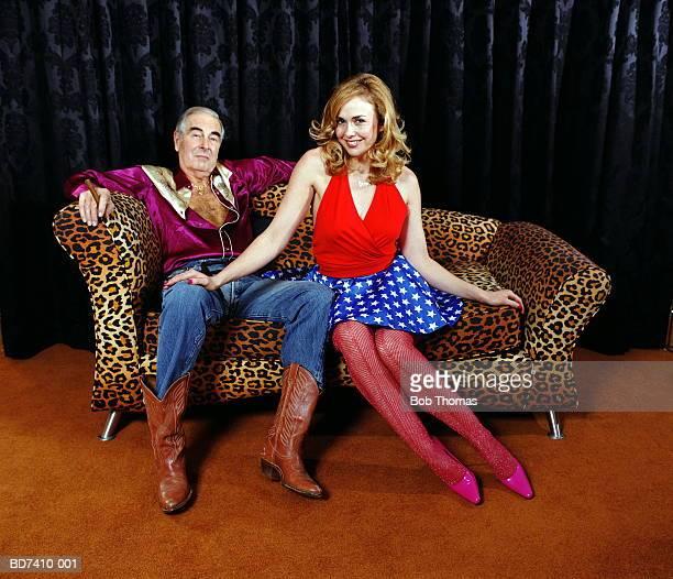 Mature man and younger woman sitting on animal print sofa