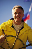 Mature man at helm of yacht