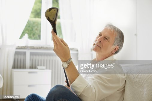 Mature man at home inspecting a golf club : Stock Photo