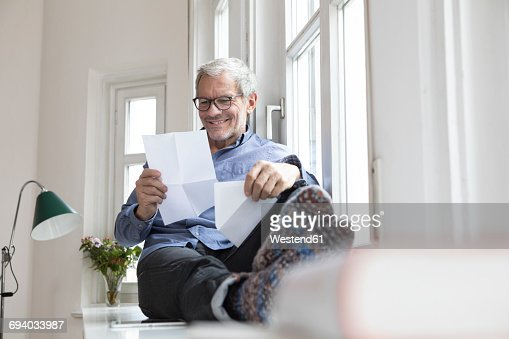 Mature man at home sitting at the window reading documents