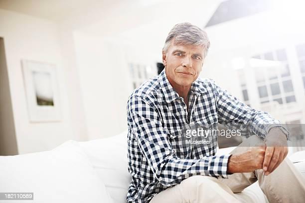 Mature man at home sitting on sofa