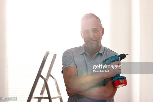 Reifer Mann zu Hause mit einer Übung-Maschine