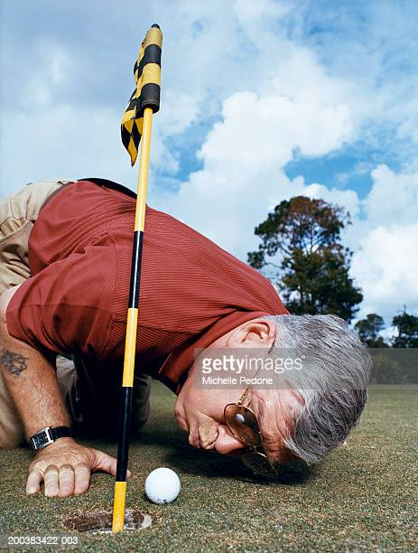 Mature man blowing golf ball into hole, ground view, close-up