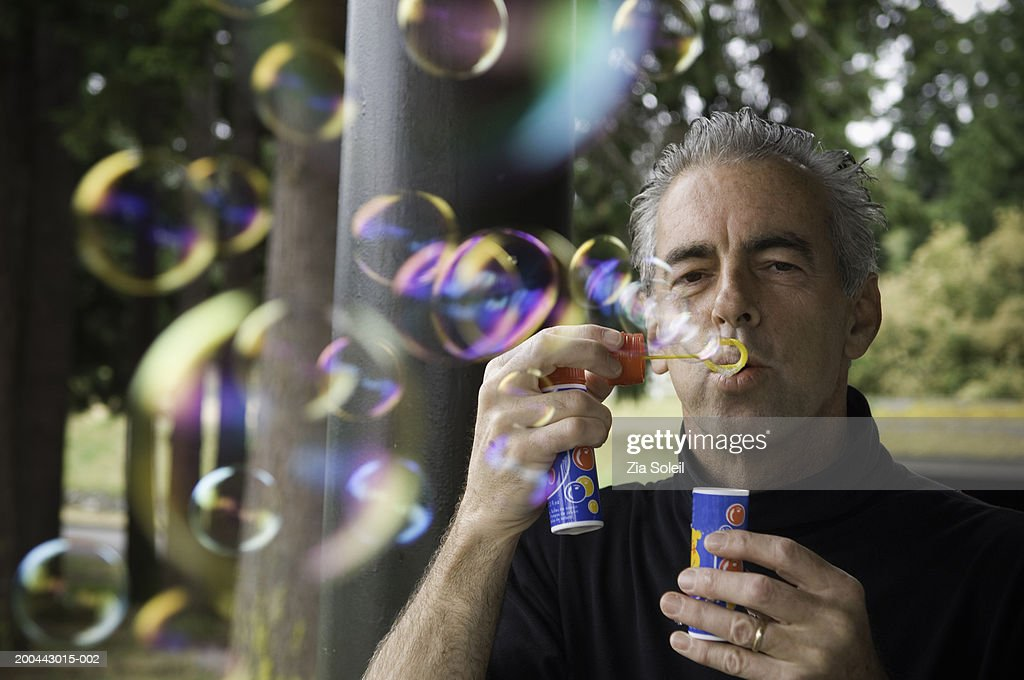 Mature man blowing soap bubbles on porch : Stock Photo