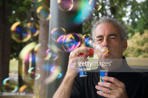 Mature man blowing soap bubbles on porch : Stock Photo