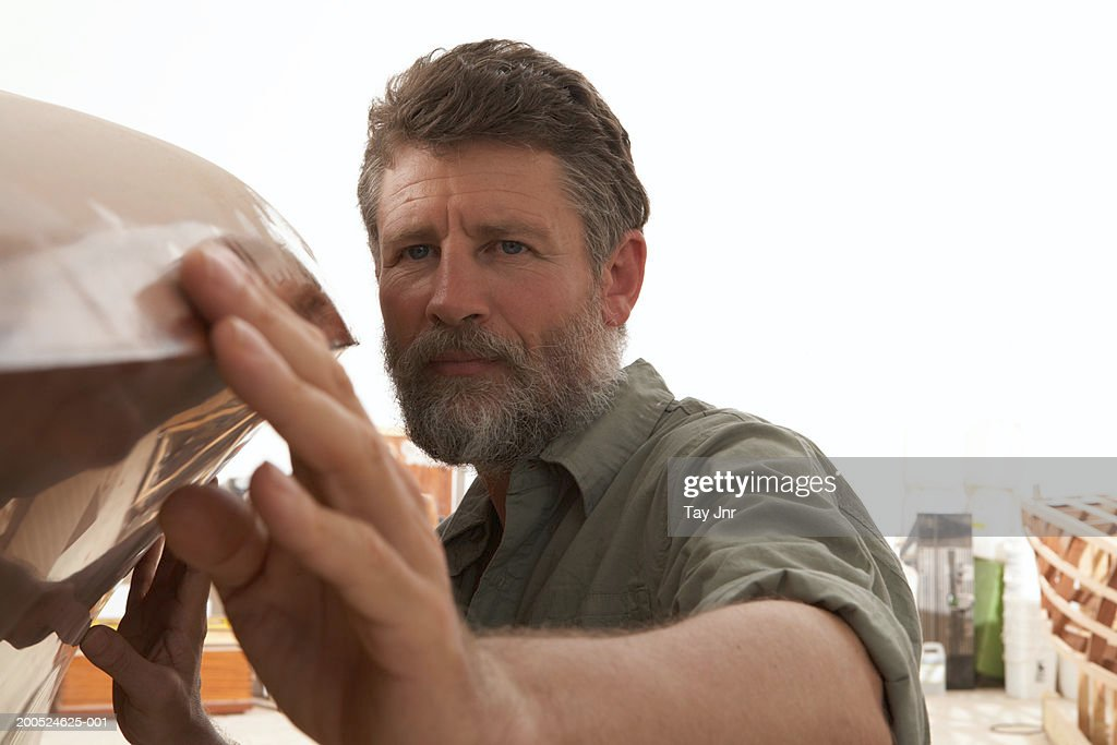 Mature man building boat in workshop, close-up : Stock Photo