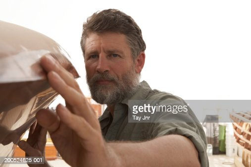 Mature man building boat in workshop, close-up : Photo