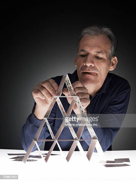 Mature man building house of cards