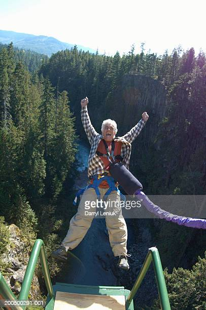 Mature man bungee jumping, elevated view, (wide angle)