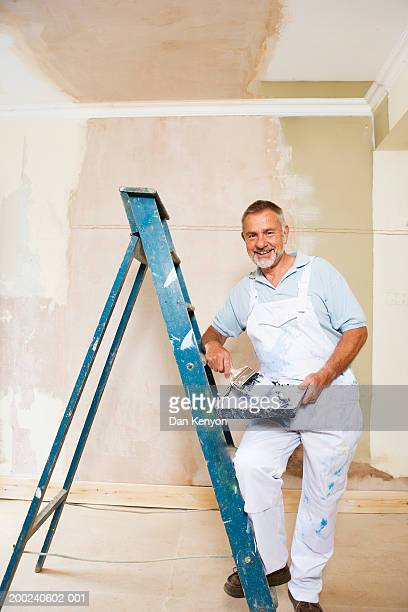Mature man by stepladder, holding paintbrush and tray, portrait