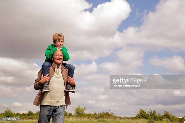 Mature man carrying boy on his shoulders