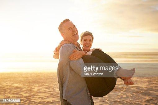 Mature man carrying girlfriend on the beach