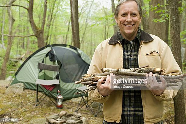 Mature man carrying logs in a forest