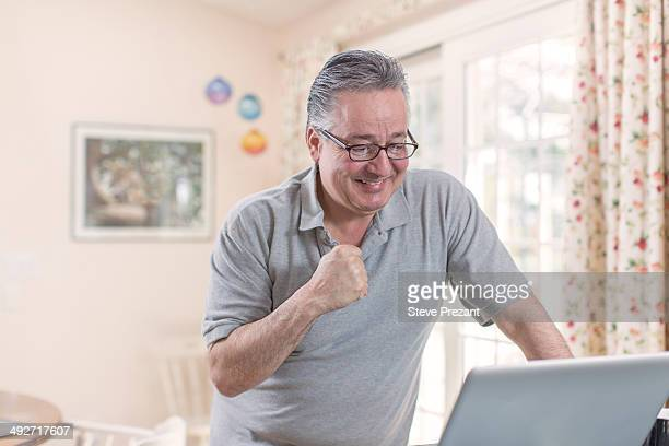 Mature man celebrating whilst looking at laptop