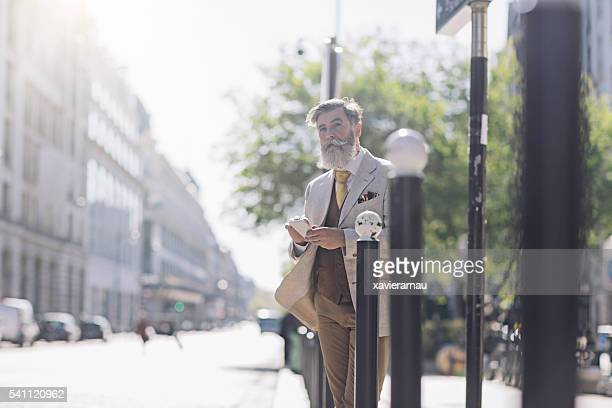 Mature man checking directions with the mobile phone in Paris