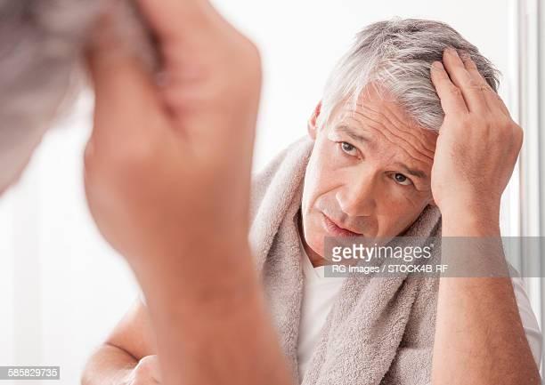 Mature man checking his gray hair in mirror