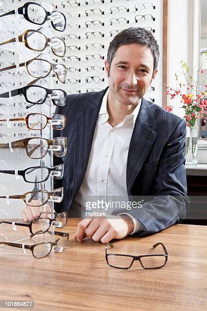 A mature man choosing a pair of eyeglasses in an eyewear store