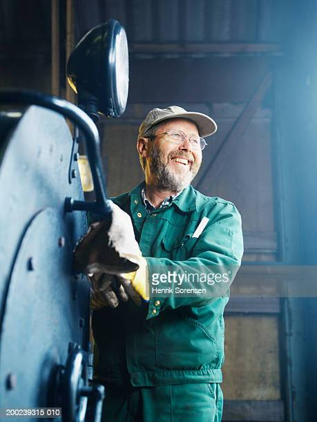 Mature man cleaning machinery, laughing, low angle view