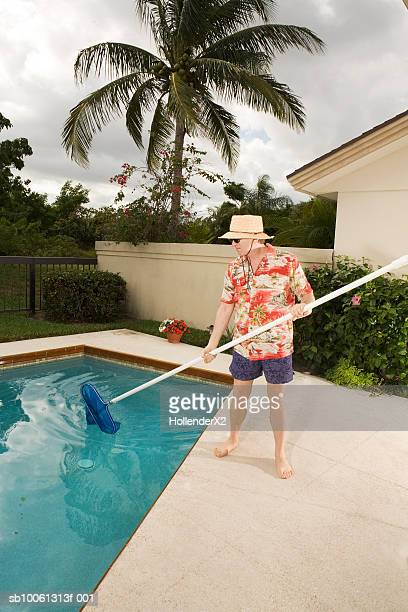 Mature man cleaning swimming pool