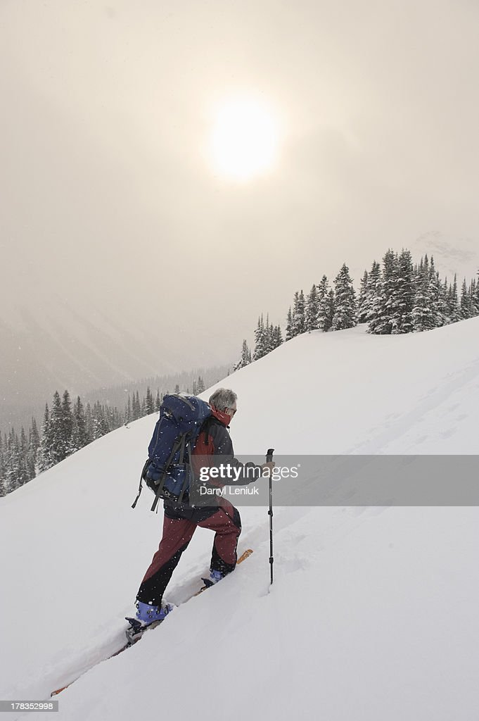 mature man climbing snowy mountain on skis : Stock Photo