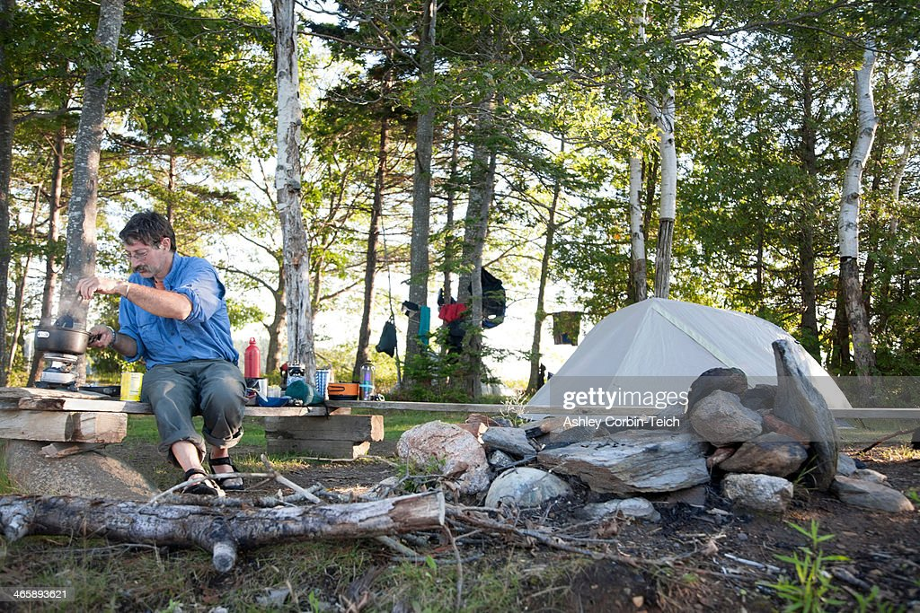 Mature man cooking on campsite, Bath, Maine, USA : Stock Photo