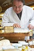 Mature man cutting brie cheese in shop