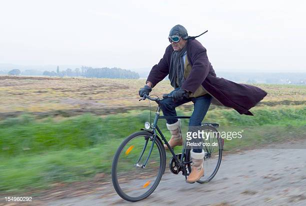Mature man cycling full speed countryside