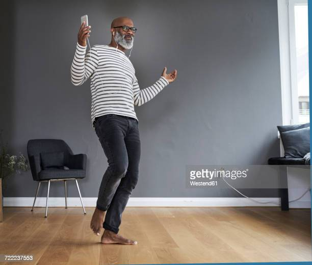 Mature man dancing alone at home, holding smart phone