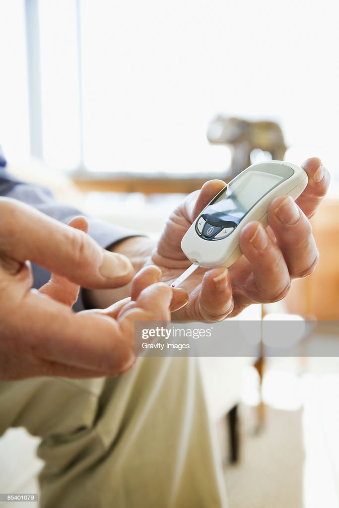 Mature man diabetic testing himself at home : Stock Photo