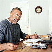 Mature man doing finances in home office, portrait