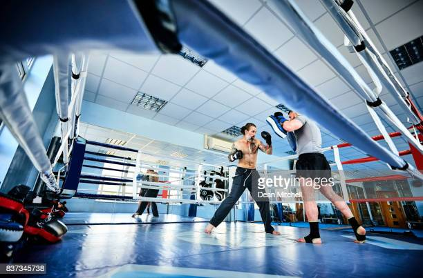 Mature man doing kickboxing training with trainer