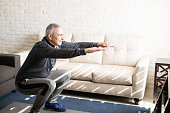 Senior man doing squats and exercising in living room at home