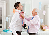 mature man doing up tie of young man.