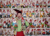 Mature man dressed as gnome with collection of gnomes, portrait