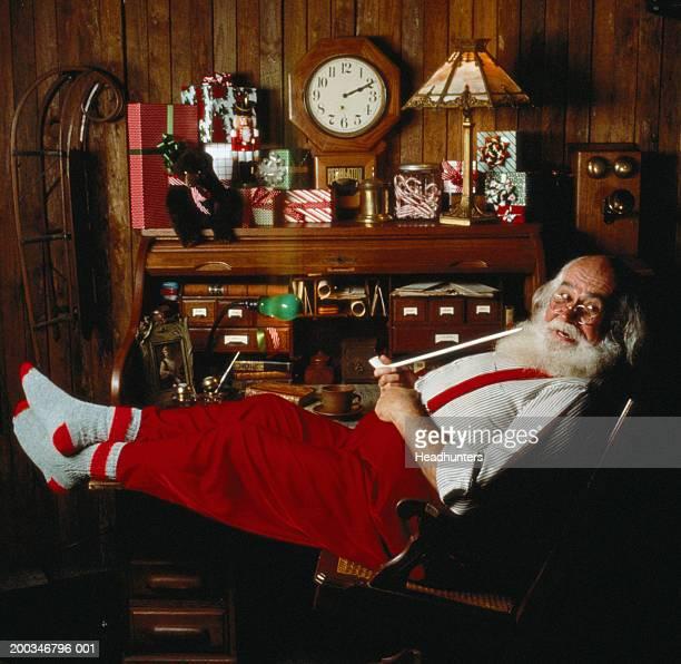 Mature man dressed as Santa Claus smoking pipe