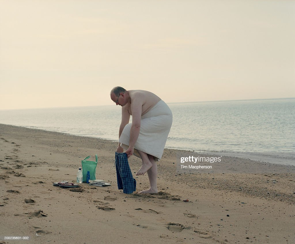 Mature man dressing on beach under towel, side view : Stock Photo