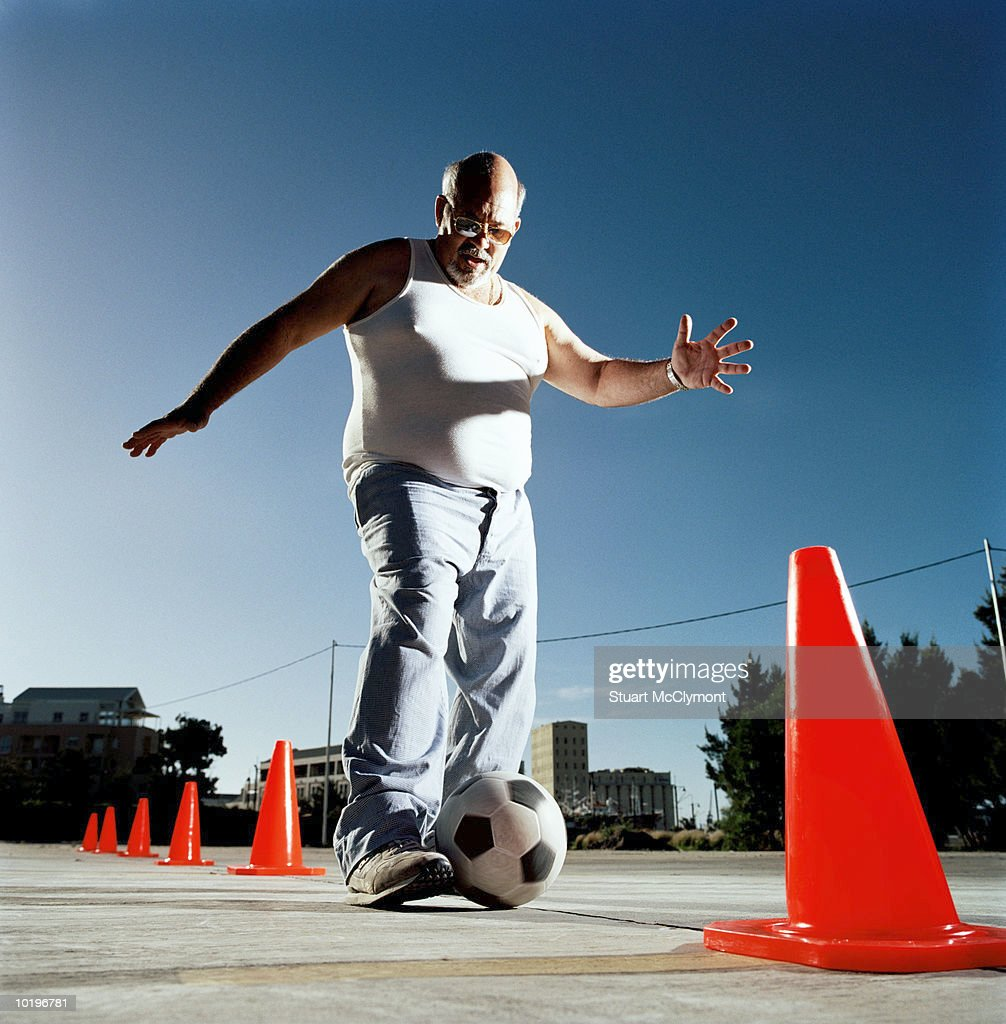 Mature man dribbling ball through cones : Stock Photo