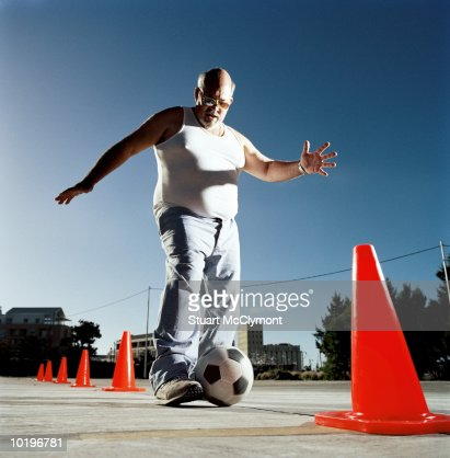 Mature man dribbling ball through cones : Stockfoto