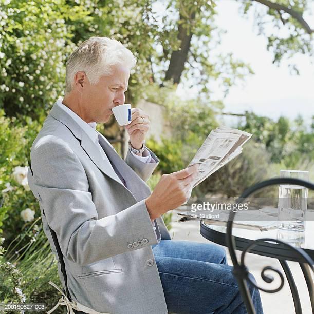 Reifer Mann, trinkt Kaffee beim Lesen der Tageszeitung