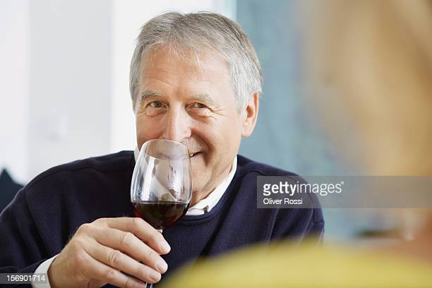 Mature man drinking glass of red wine