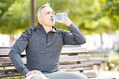 Fit mature man drinking water and taking a break from workout outdoors in a park