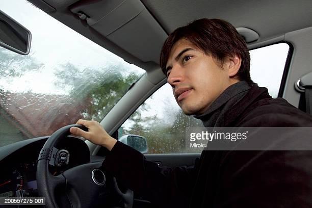 Mature man driving car, close-up